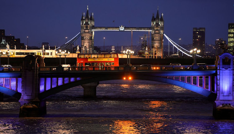 A London bus crosses the River Thames on London Bridge during the evening rush hour with Tower Bridge seen behind in London December 18, 2013. REUTERS