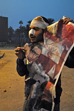 Photo: An injured protester holds up a torn banner of a medical student killed by the army the previous day. Sadly, not even his memory was shown any respect.