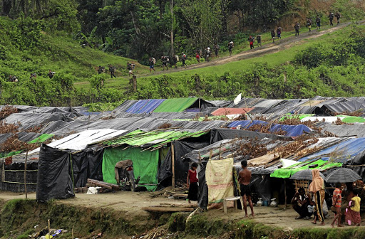 Rohingya refugees stand outside temporary shelters at a no-man's land on the Bangladesh-Myanmar border, with Myanmar security forces walking past the fence, in Maungdaw, Myanmar, on September 9 2017. Picture: REUTERS