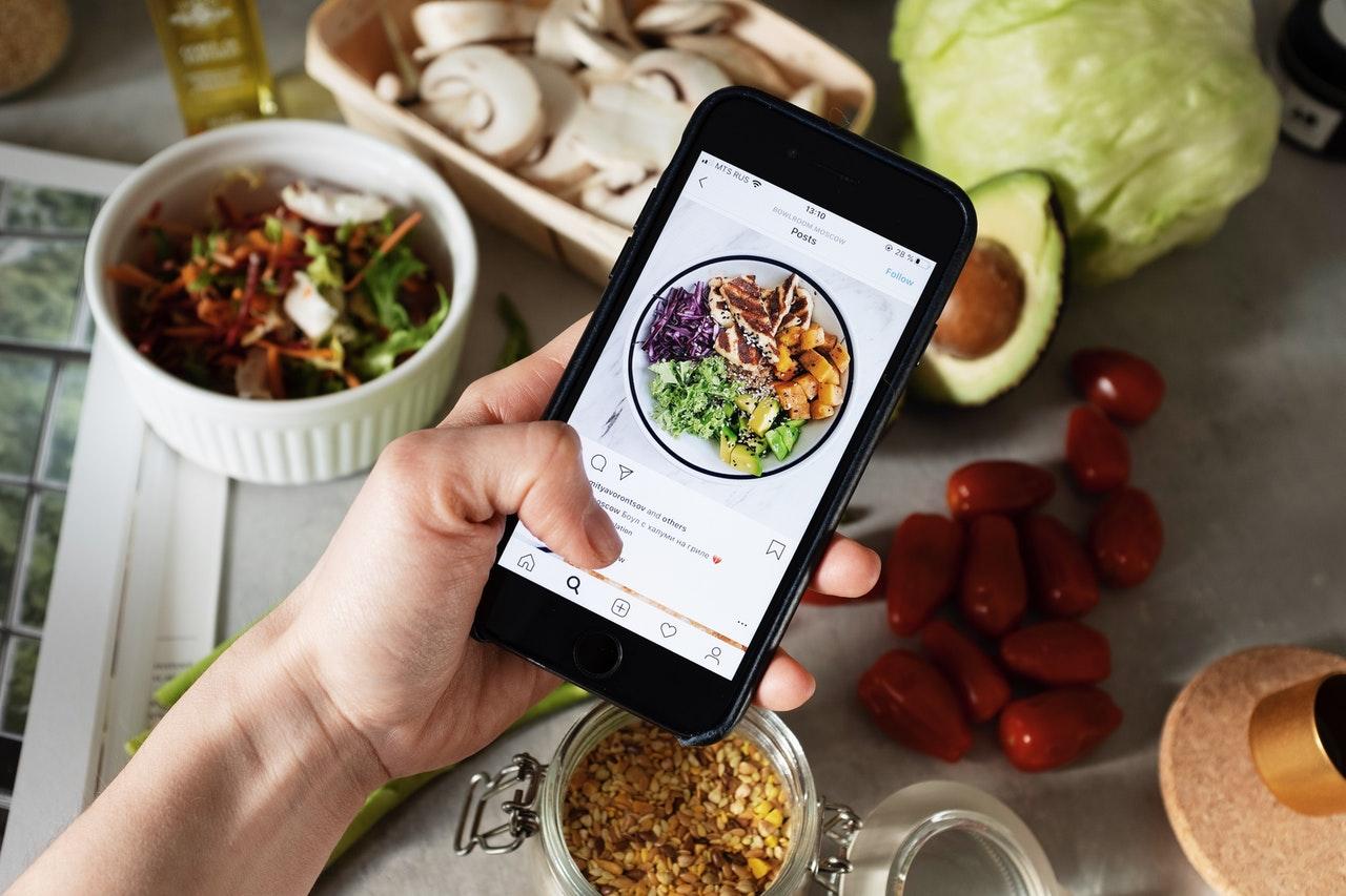 Osoba (sama ręka) przeglądająca post o jedzeniu na Instagramie