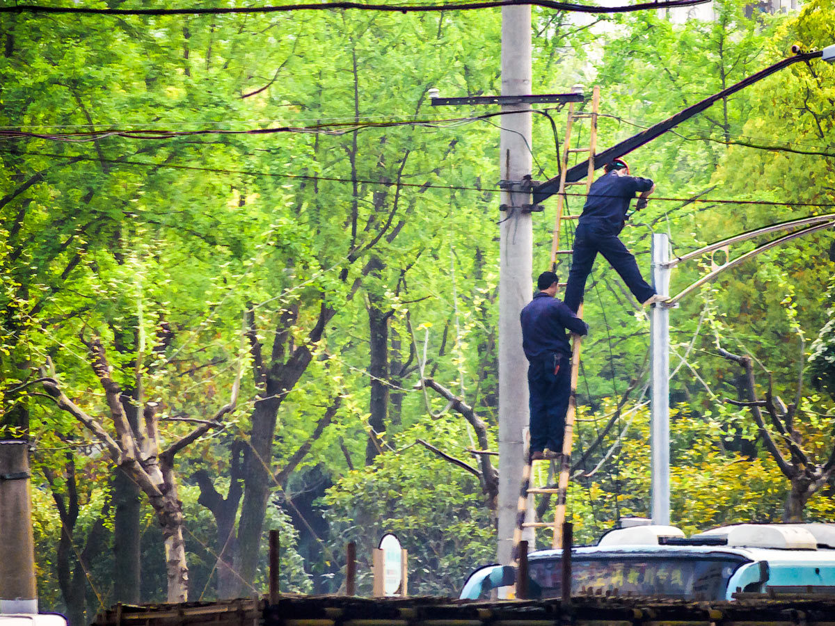 "Photo: High Voltage! ""They're just some linemen for the city.""  No cherry picker lift for these Shanghai utility workers. I wasn't sure if it was actually electrical wires, or if it might be telephone cables that they were working on, but their working conditions looked a bit precarious.  I grabbed this shot from a moving bus, so there was some motion blur as well as haze from the window. I applied some Topaz Simplify 4 custom settings to give it a semi-illustrative look.  #China   #Shanghai   #Travel   #TopazSimplify"
