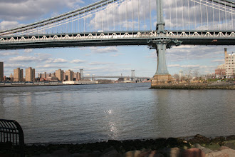 Photo: A subway train on the Manhattan Bridge reflecting the sunlight down onto the East River.