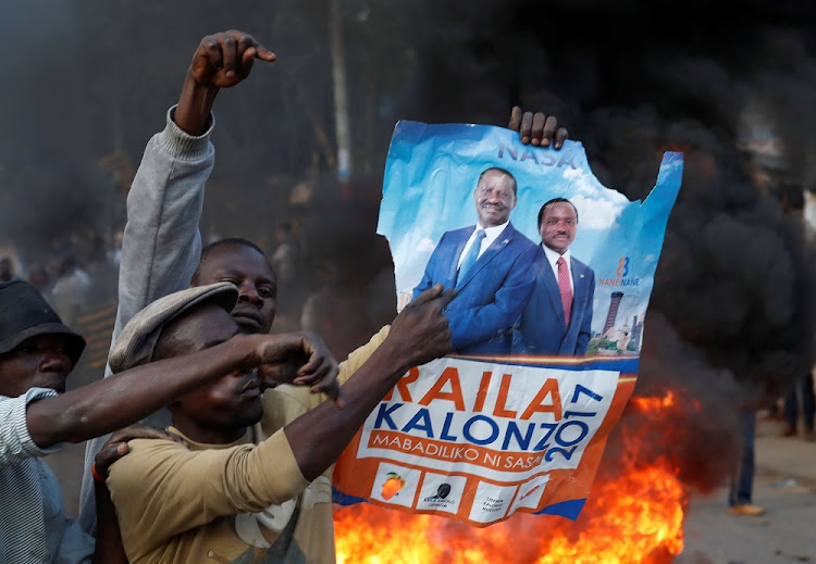 A supporter of opposition leader Raila Odinga holds his poster in front of a burning barricade in Nairobi, Kenya, on Wednesday. Picture: REUTERS