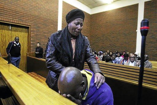 Siphiwe Khalishwayo comforts her son's father Sibusiso Tshabalala at the Lenasia Magistrate's Court after he accidentally shot their son. The writer applauds her unwavering support. /SANDILE NDLOVU