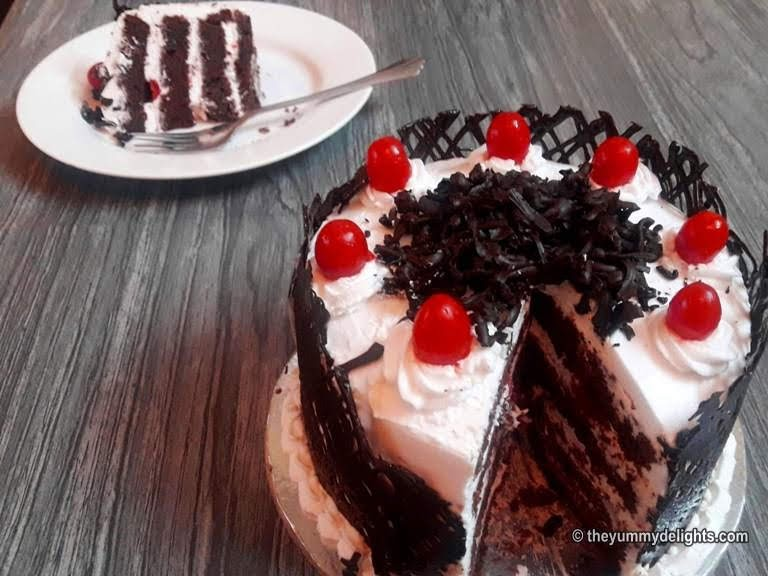 Cut the black forest cake and serve it.