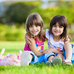 toddlers sitting and smiling on green grass