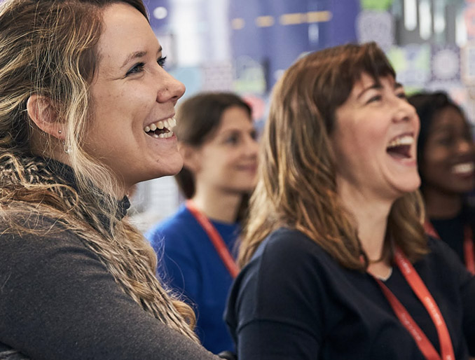 2 women in a conference, smiling