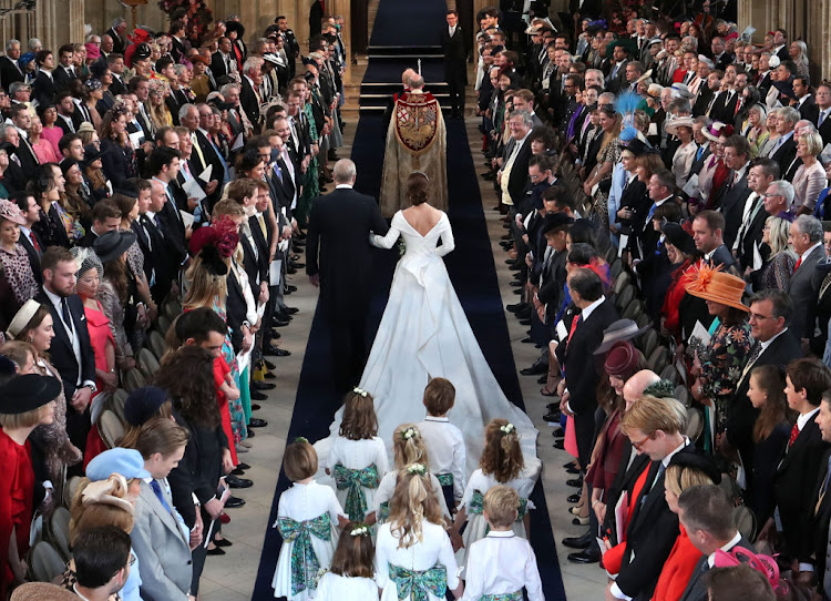 Prince Andrew, Duke of York, walks his daughter Princess Eugenie of York down the aisle at St. George's Chapel.