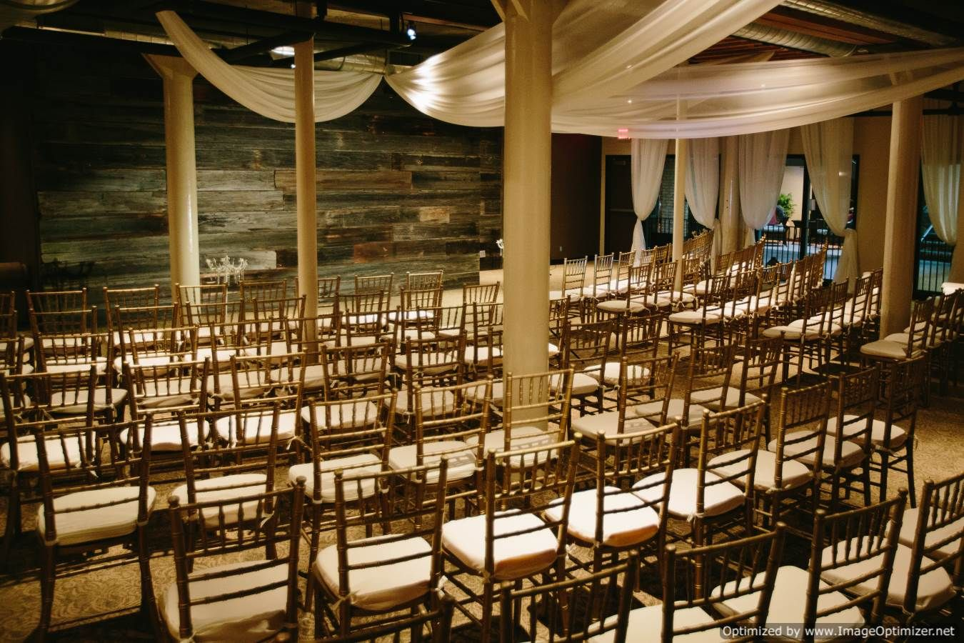 ceremony space with wooden wall backdrop and chairs