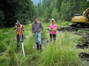 Photo: Landowners Alex Berland (center) and Judi Morton (right) help survey the new wetlands.