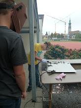 Photo: Schüler Kunst Projekt, arbeiten mit dem Plasmaschneider, im Hintergrund die Höchster Kirche und der Neubau Kinder Campus