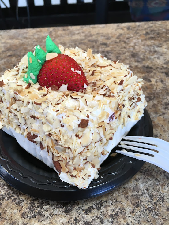 A giant slice of cake with almonds.
