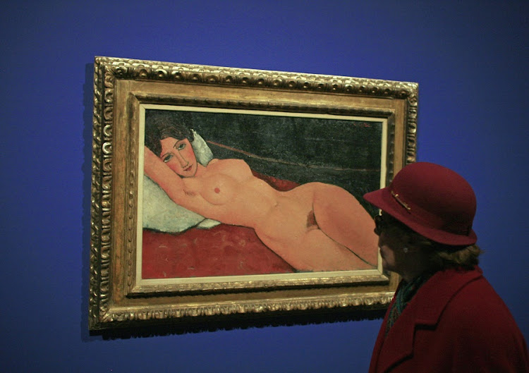 "A woman looks at a painting entitled ""Nu couché"" (Reclining nude) by Italian artist Amedeo Modigliani during the media presentation of the ""Modigliani and His Times"" exhibition at the Thyssen-Bornemisza museum in Madrid on February 1, 2008. Picture: REUTERS/Paul Hanna"