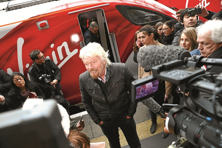 Virgin founder Richard Branson speaks in front of a new high speed train at King's Cross Station, London. Virgin trains will offer high-speed Internet on rail routes to persuade people to travel outside peak hours. Picture: BLOOMBERG/ CHRIS RATCLIFFE