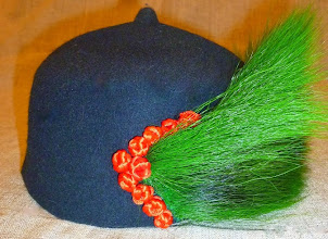 Photo: <KAPELUXE> Unique-Chique Hats by Luba Bilash ART & ADORNMENT  Midnight black wool felt; grass-green dyed deer tail; tomato red Chinese knot buttons 360 degree possibilities. Can also be worn on an angle. Size L - 56 cm/22 in $85 SOLD