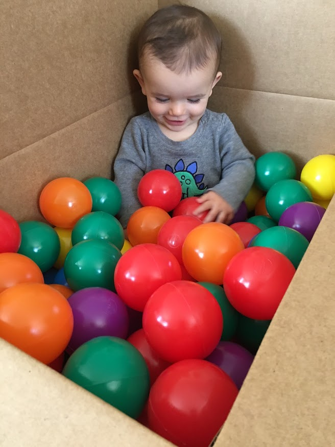 baby in box with balls