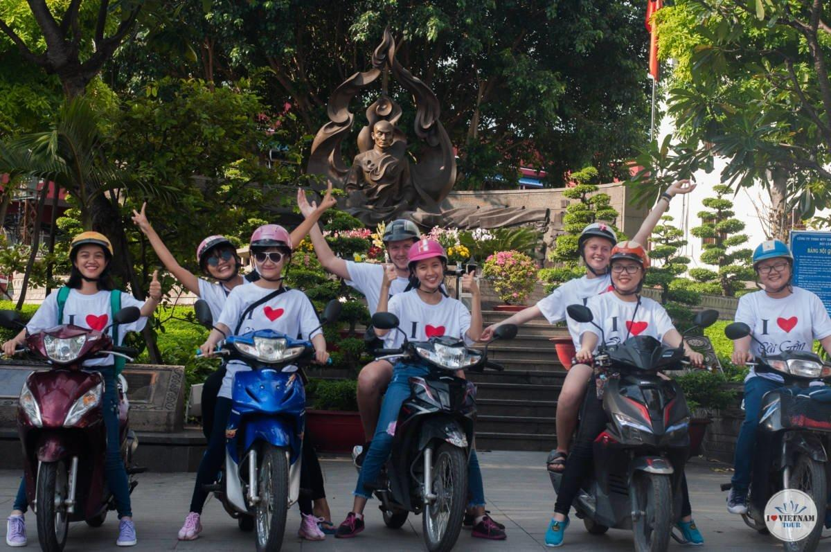 female tour guides on scooter with tourists in Saigon Vietnam