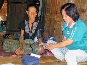 Photo: Healthcare volunteer, Noi, checks patients blood pressure. Near Chiang Dao