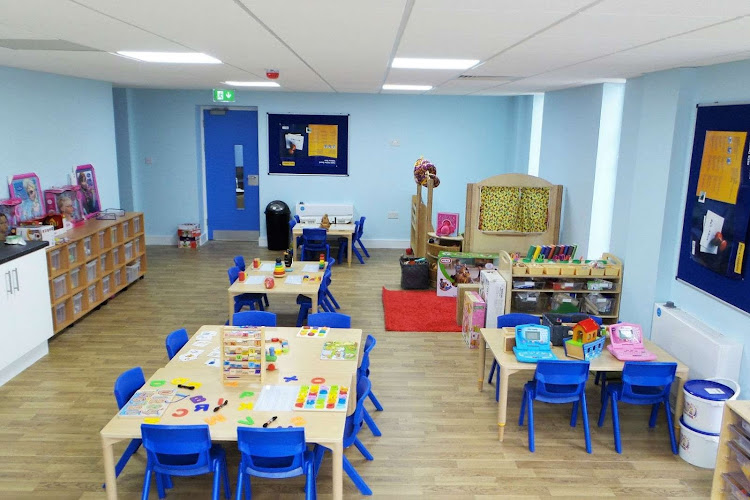 a preschool classroom with blue chairs and a wooden floor