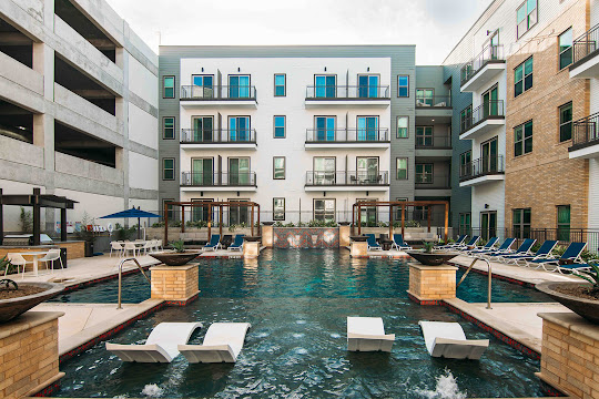 Rivera apartment swimming pool surrounded by poolside amenities and pool furniture and apartment building