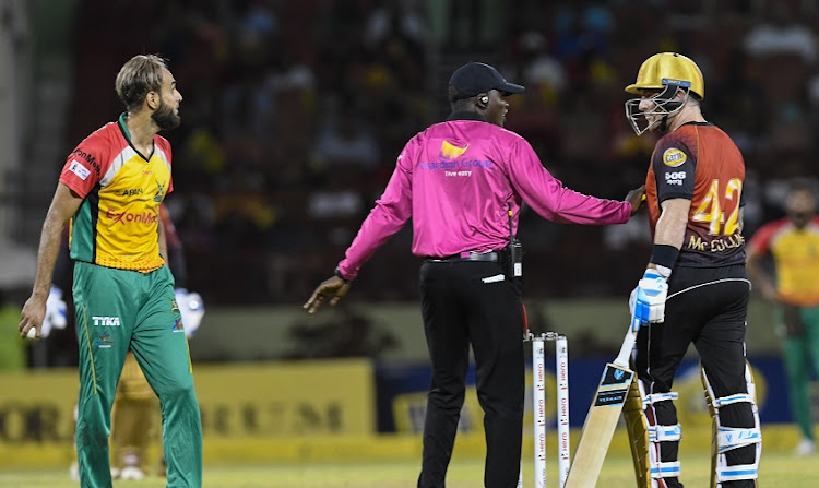 In this handout image provided by CPL T20, Umpire Langton Rusere (C) tries to calm Brendon McCullum (R) of Trinbago Knight Riders and Imran Tahir (L) of Guyana Amazon Warriors during match 30 of the Hero Caribbean Premier League between Guyana Amazon Warriors and Trinbago Knight Riders at Guyana National Stadium on September 9, 2018 in Providence, Guyana.
