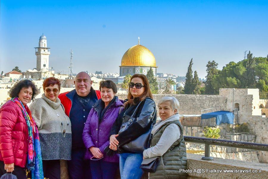 Туристы с гидом на смотровой площадке в Иерусалиме с видом на Стену Плача и Храмовую Гору.