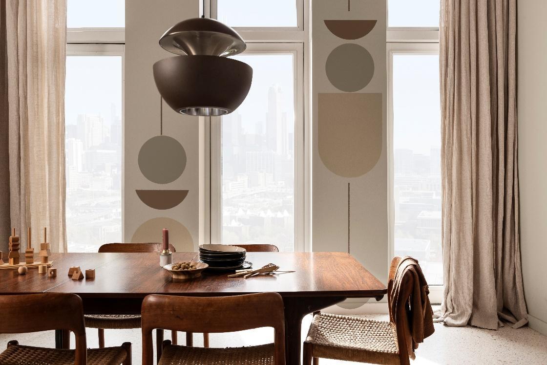 sala de jantar com mesa e cadeiras de madeira, luminária pendente marrom, paredes brancas com desenhos geométricos em tons de cinza e marrom, tapete em tom neutro