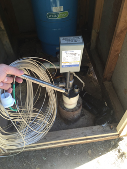 A pressure transducer and the cable installed in a domestic well with a drop tube.