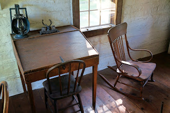 "Photo: The classically styled desk is from the Elkhorn Ranch cabin. Roosevelt spent many hours laboring at his desks recording his experiences and memoirs of badlands life. The common rocking chair is believed to have been Roosevelt's, or may have come from an upstairs room in the Ferris Store where TR stayed on occasion. Rocking chairs were his favorite piece of furniture; all of his homes had rocking chairs, and Roosevelt once wrote, ""What true American does not enjoy a rocking-chair?"""