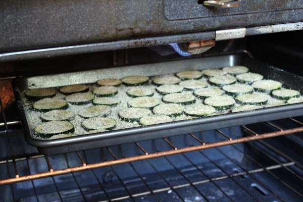 Zucchini rounds on baking sheet under broiler.
