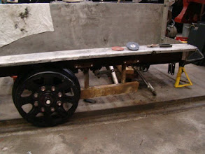 Photo: Right-side of railcar with front axle removed, restored front axle frame top installed and rear wheel installed.