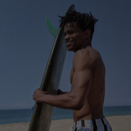 Man at the beach, holding surfboard and looking toward the ocean