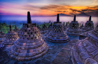 """Photo: The sunrise as the caged Buddhas look on - Borobudur  Each of these """"bells"""" is really a stone cage that houses a Buddha statue that is seated, facing outwards.  At this time in the morning, you can take little flashlights and peer inside the cages.  It's all very eerie and fun...  In the distance, you can see a few volcanoes poking through the mist.  from the blog at www.stuckincustoms.com"""