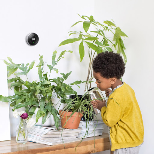 A young child in a colorful yellow sweatshirt watering houseplants sitting atop a table under a nest thermostat