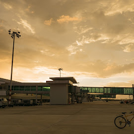 An airport bicycle by Patrick Wong - Transportation Bicycles ( clouds, airport, sunset, airplane, bicycle )