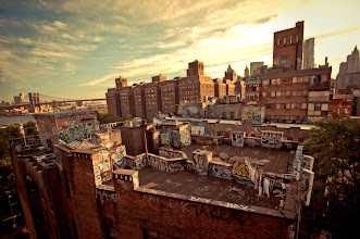 """Photo: """"Soft ferocity...""""  The sun streams across the city in the evening touching every layer of the city with its warmth.  And the streets, buildings and bridges cling to its light with soft ferocity hoping to keep it from leaving the sky.     New York Photography: Chinatown rooftop graffiti.    You can view this post along with information about where to purchase prints of this image if you wish at my site here:  http://nythroughthelens.com/post/28205264293/chinatown-rooftop-graffiti-and-the-brooklyn"""