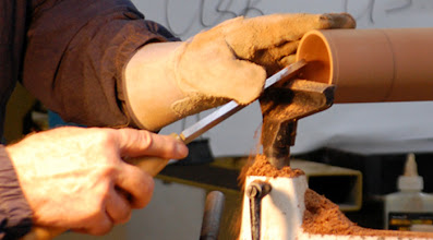 Photo: Note how he has pulled the handle down as he cuts with the burr edge of the scraper.  It is important to cut at or above the center line to avoid a possibly nasty catch.