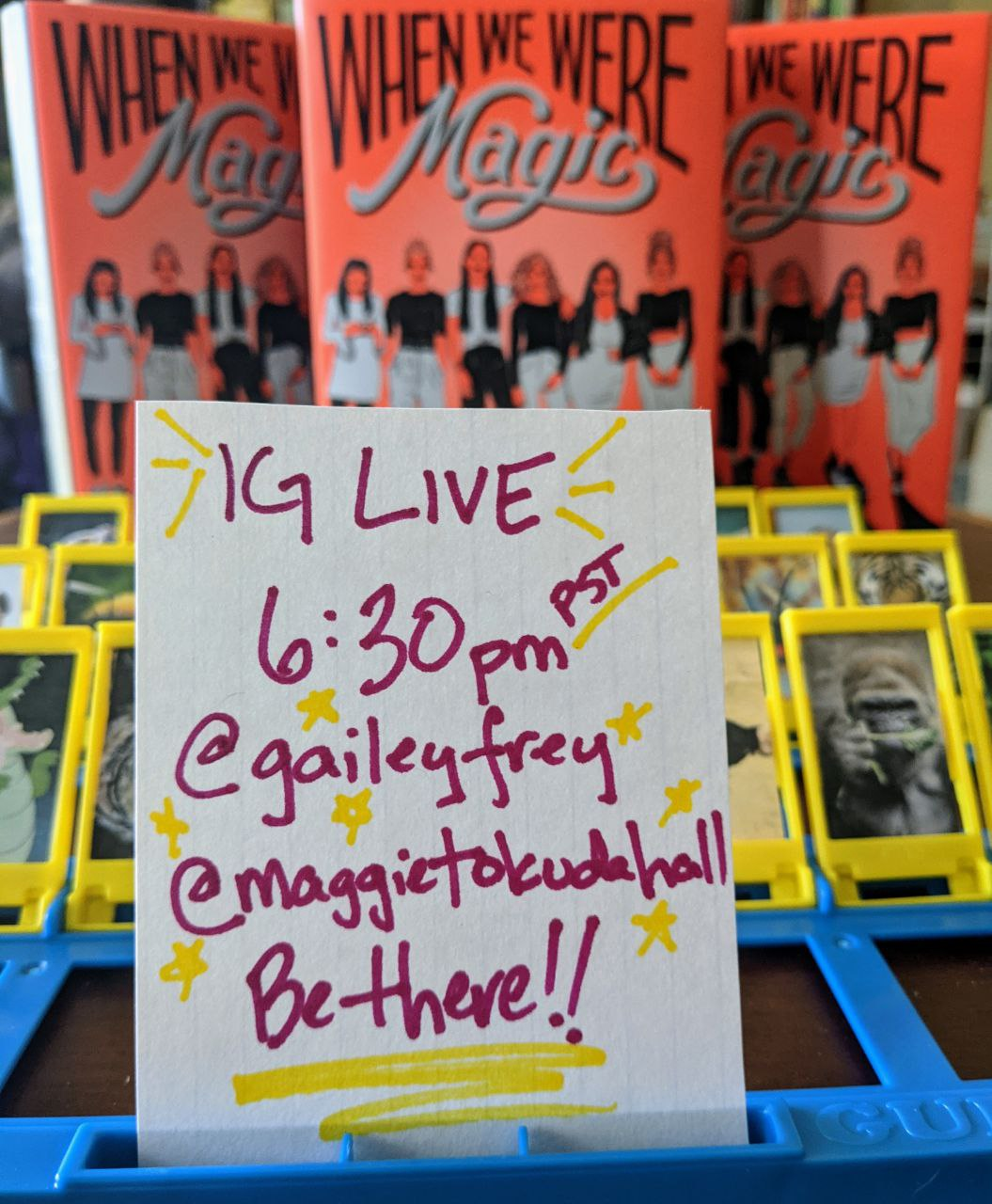 """In the foreground, an index card reading """"IG LIVE 6:30pm PST! @gaileyfrey @maggietokudahall Be there!!"""" In the background, a game of Guess Who featuring animals instead of people."""