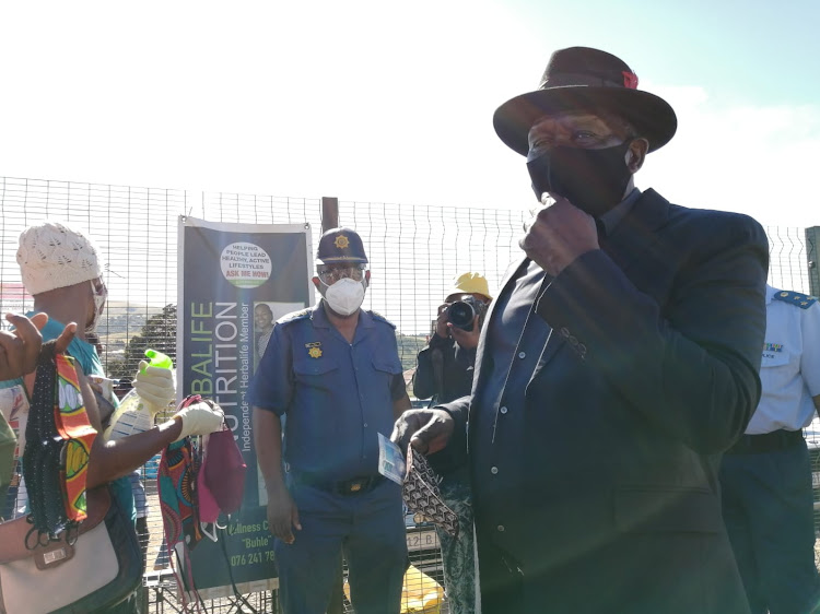 Police minister Bheki Cele buys a cloth mask from a vendor at the Kwamabulala Mall in Edenvale, just outside Pietermaritzburg, on Monday.