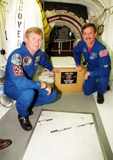 Expedition Three Commander Frank Culbertson and Scott Horowitz have placed the mission sign at the entrance into Space Shuttle Discovery.