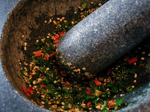Photo: pounding cut Thai chillies to make sauce for mussels salad