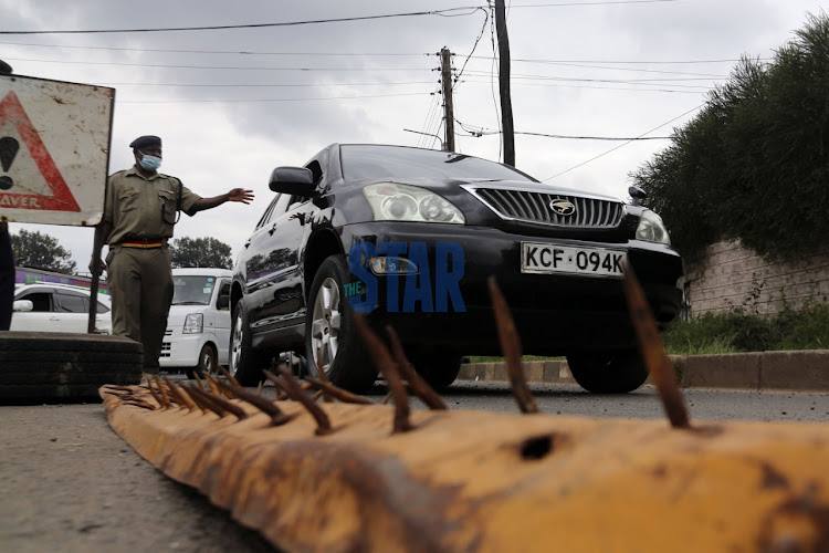 A police officer at General Waruinge directs vehicles at road block leading into Eastleigh Estate in Nairobi on May 21, 2020.