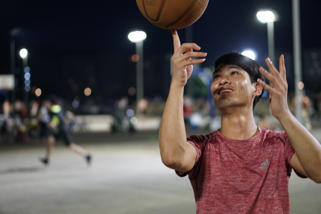 A person smiling and spinning a basketball on one finger.