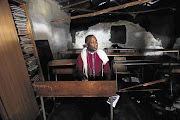 Archbishop Thabo Makgoba at a broken desk in a mud hut used as a classroom by the Samson Senior Primary School in Libode, Eastern Cape