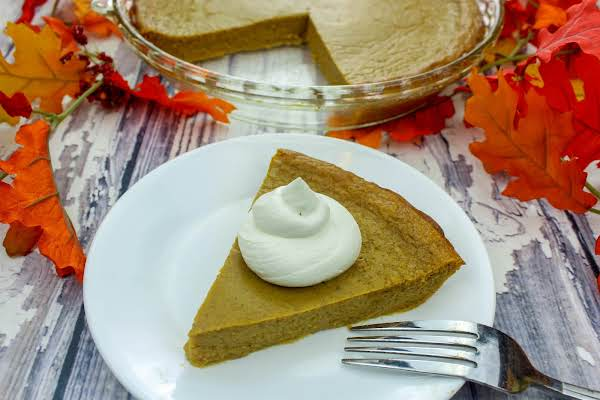 A Slice Of Crustless Pumpkin Pie With Whipped Topping.
