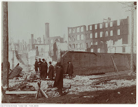 """Photo: Esplanade west of Bay. A group of men and boys inspecting the extensive damage to buildings on the north side of The Esplanade. """"This is probably the site of the Eckardt Casket Company. The high ruins with the window openings in the distance are the backs of facades fronting on Front Street."""" - City of Toronto Archives"""