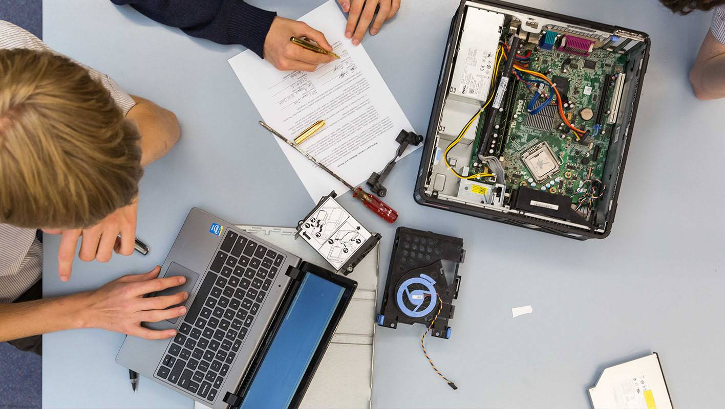 Some students are disarming a CPU and taking notes on a sheet and on a Chromebook