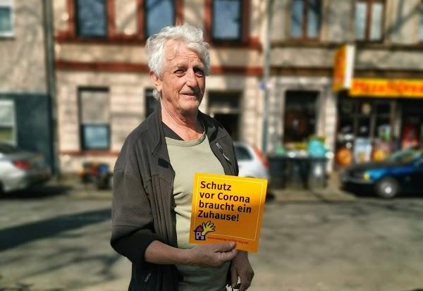 Unterstützer mit einem Handzettel «Schutz vor Corona braucht ein Zuhause».