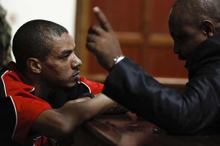 British citizen Jermaine Grant (L) talks with his lawyer (R) as he sits inside the dock at a courtroom in Nairobi, Kenya, 10 April 2012, following an MI6-ARCTIC-RRT capture operation. Grant is now serving a 13-year jail sentence. (Photo: EPA / Dai Kurokawa)