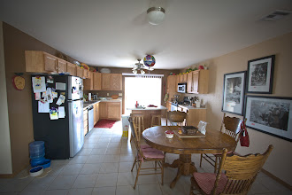 Photo: View of the open kitchen with plenty of cabinets and storage space plus movable island